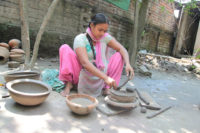 an women is making bowl with clay