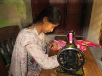 a lady is stiching cloth with sewing machine